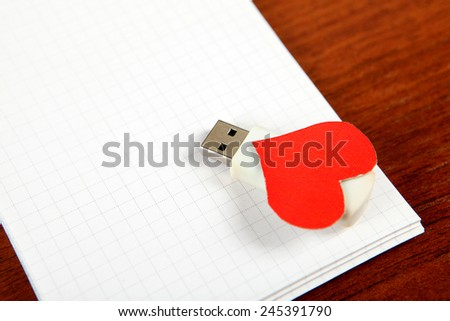 USB Flash Drives with Heart Shape on the Blank Note Pad - stock photo