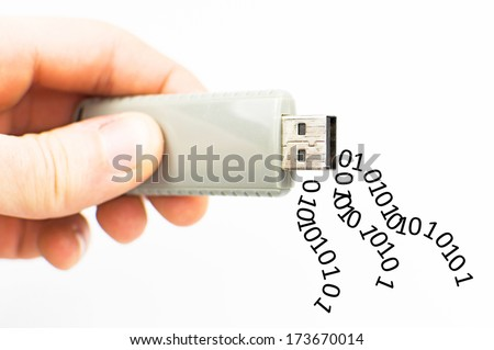 USB stick in hand with leaking data - stock photo
