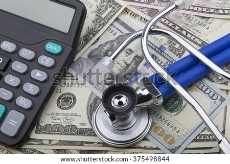 USD bank notes with a stethoscope and calculator showing the high cost of health care