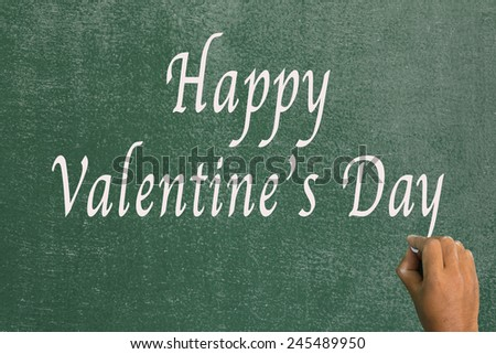 Use chalk to write the word happy valentine's day on the board. - stock photo
