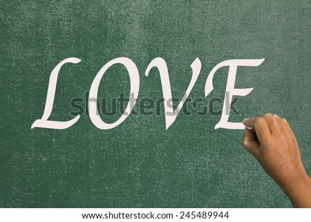 Use chalk to write the word love on the board. - stock photo