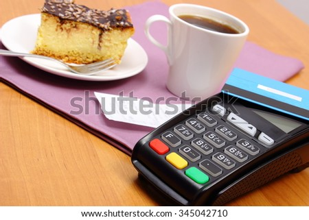 Use payment terminal and credit card for paying in cafe or restaurant, cheesecake and coffee, enter personal identification number, polish receipt, finance concept - stock photo