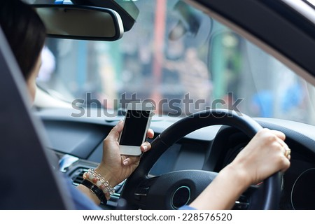 Use smart phone in hand while driving - stock photo