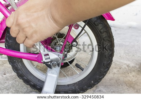 Use the wrench to tighten wheel bicycle - stock photo