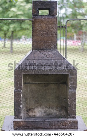 Used barbecue made from stone in park with trees and a fence in the background