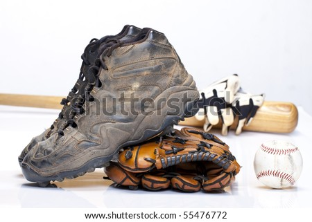 Used baseball cleats against a glove, ball, bat, and batting gloves on a white background - stock photo