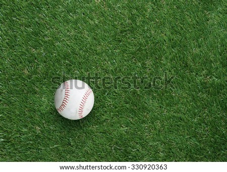 used baseball on green grass with copy space.