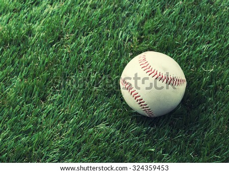 Used baseball on green grass with copy space - vintage filter.