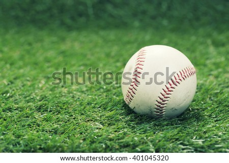 Used baseball on green grass with copy space - vintage filter. - stock photo