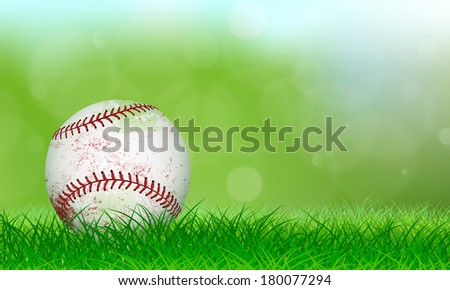 Used baseball sitting on lush grass in front of a soft background - stock photo