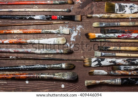 Used brushes for painting lie on the old wooden rustic table  - stock photo