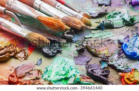 used brushes in an artist's palette of colorful oil paint for drawing and painting - stock photo