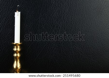 Used candle with shiny brass candlestick put on the black color leather surface background represent the  Buddhistic religion blessing equipment related. - stock photo