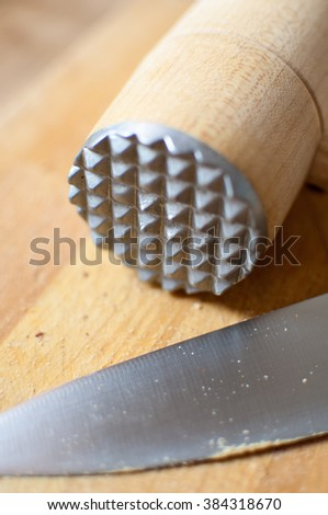 Used chopping knife & kitchen hammer on a wooden table. - stock photo