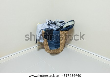Used clothes in wood basket at corner in room - stock photo