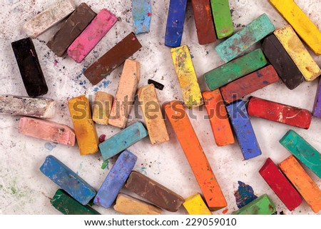 Used colorful Pastel art sticks viewed from above on a white background - stock photo