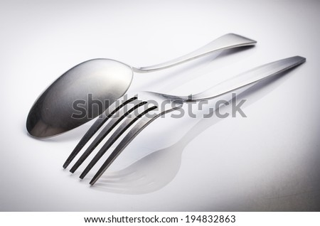 Used Cutlery set with Fork and Spoon isolated on gray background .