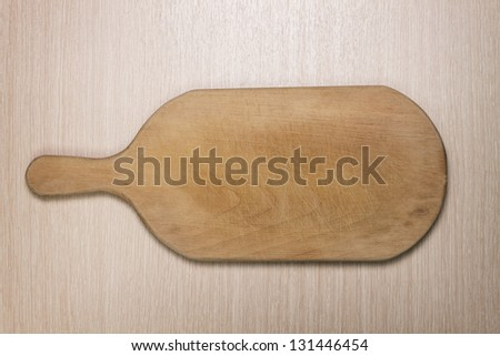 used cutting board on the wooden table - stock photo