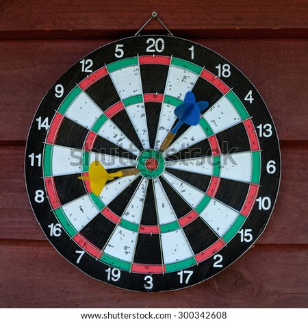 Used dartboard with two darts over wooden background - stock photo