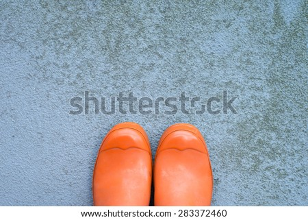 used, dirty, orange rubber wellington boots on a grungy concrete surface with lots of copy space, top view, horizontal - stock photo