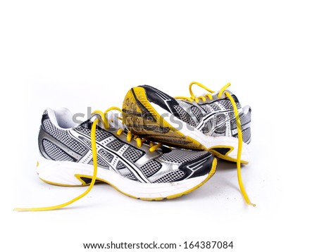 Used dirty pair of running shoes over a white background - stock photo