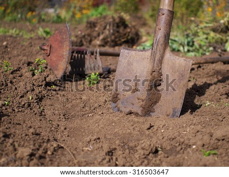 used dirty shovel in front of gardening tools, shallow depth of field