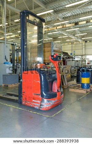 Used forklift truck is standing inside the production hall. All potential trademarks are removed.