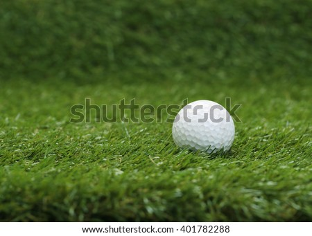 Used Golf ball on the green grass. - stock photo