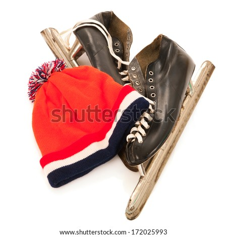 Used male ice skates and orange dutch hat isolated over white background