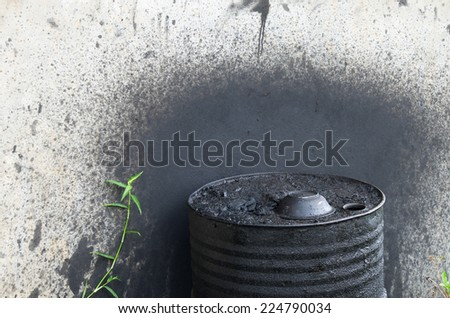 used oil engine in fuel tank  and green grass beside. - stock photo