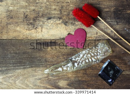 used (open) condoms and red love heart, flower  on wooden background. space for text. valentine days, dating, making love concept - stock photo