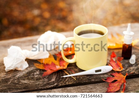 Used paper tissues and mug with hot tea and thermometer along with pills and nose drops on wooden surface, flu season in autumn