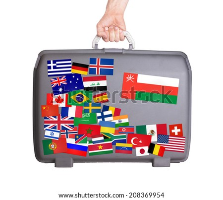 Used plastic suitcase with lots of small stickers, large sticker of Oman - stock photo