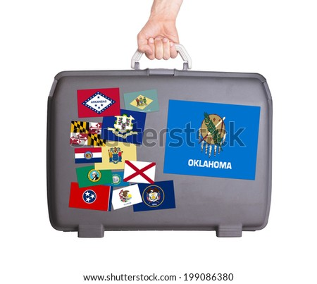 Used plastic suitcase with stains and scratches, stickers of US States, Oklahoma - stock photo