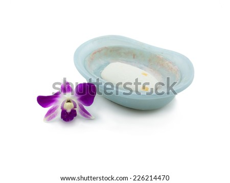 Used soap on a soap-dish, purple orchid decorated with isolated on white background - stock photo