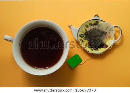 used tea bag, tea and a plate, stylized as a teapot - stock photo