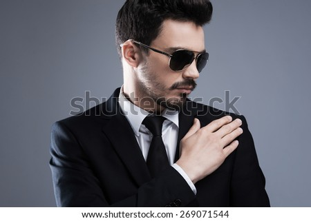 Used to perfection and success. Handsome young man in formalwear and sunglasses adjusting his jacket while standing against grey background - stock photo