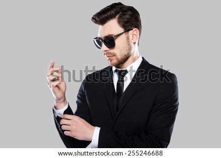 Used to perfection. Handsome young man in formalwear adjusting his sleeve while standing against grey background