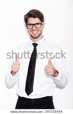 Used to success. Confident young man showing his thumbs up and smiling while standing against white background - stock photo
