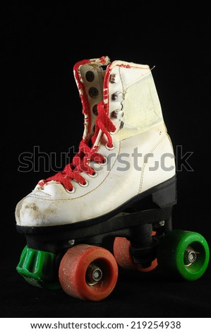 Used Vintage Consumed Roller Skate on a Black Background - stock photo