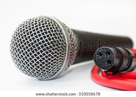 Used vocal microphone with red xlr cable on the white background. - stock photo