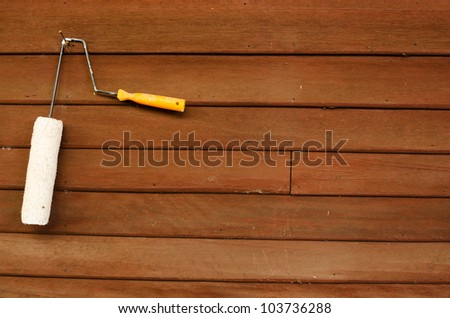 used white roller brush hanging on wooden wall