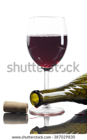 Used wine bottle, glass of wine and cork on white background