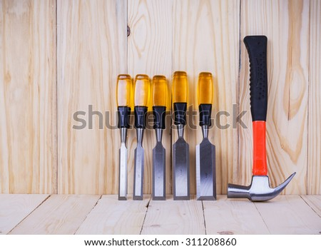 used wooden hammer and chisel on wood background. These work tools are used by the carpenter.