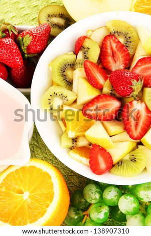 Useful fruit salad of fresh fruits and berries in bowl close-up