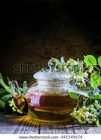 Useful linden tea in glass teapot, branches linden flowers and leaves, vintage wooden background, selective focus - stock photo