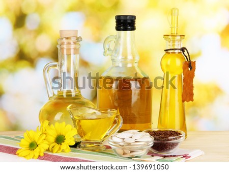 Useful linseed oil and pumpkin seed oil on wooden table on natural background - stock photo