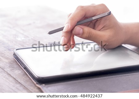 Uses Mobile Phone tablet on woodtable