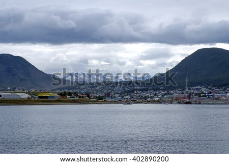 Ushuaia, Argentina seen from the water, as a boat pulls away, into the Beagle Channel off the Straight of Magellan, with hills and snow covered mountains in the background - stock photo