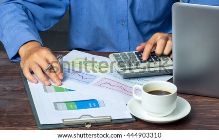 using a calculator to calculate the numbers - stock photo